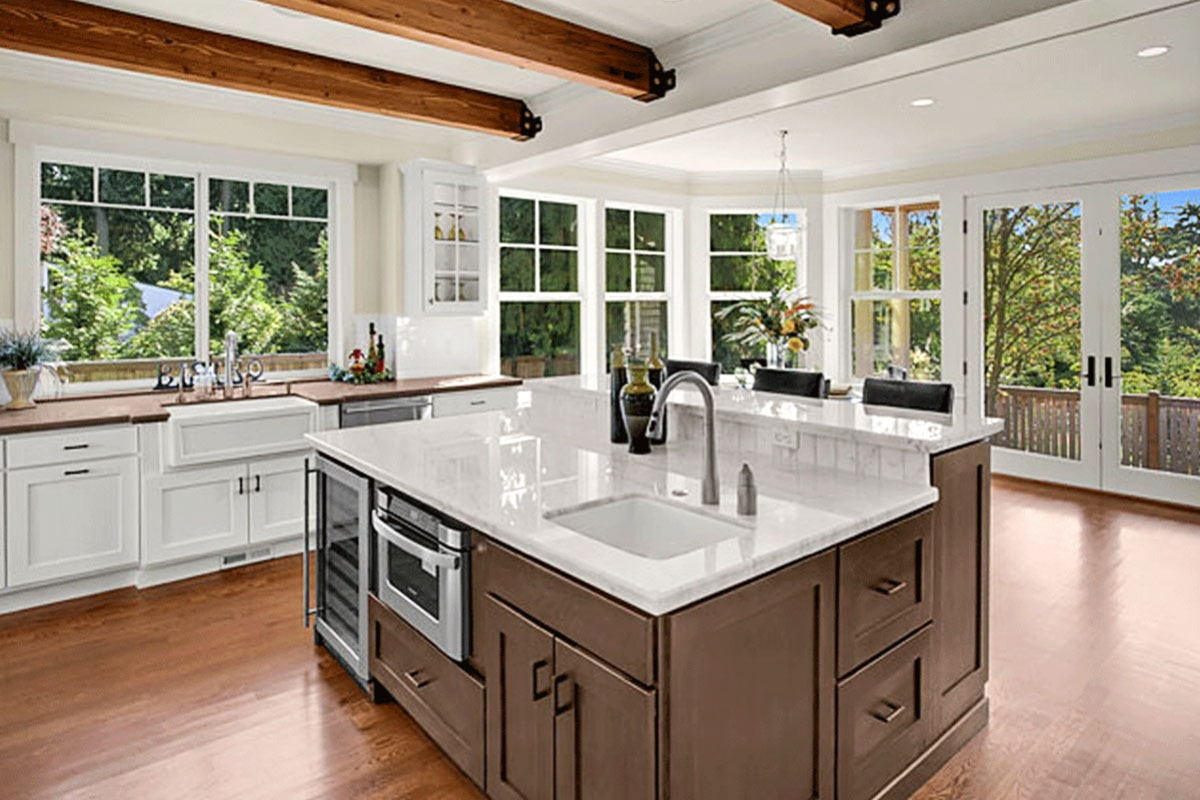 The kitchen is surrounded by glass windows and doors bringing an abundance amount of natural light in.