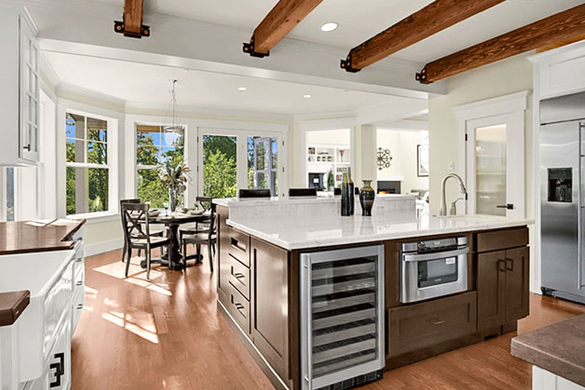 The center island is fitted with a sink, an oven, and a beverage fridge.