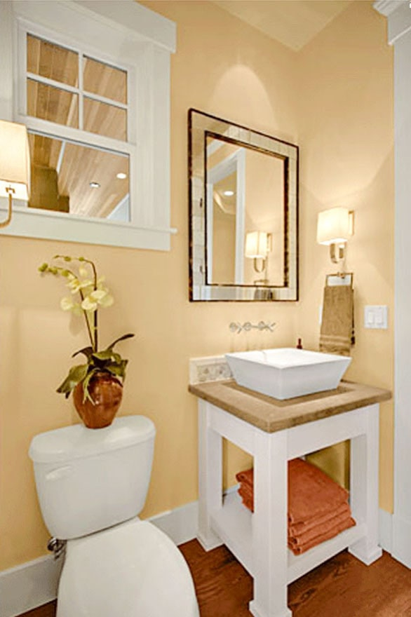 Powder room with a toilet and a washstand topped by a vessel sink.