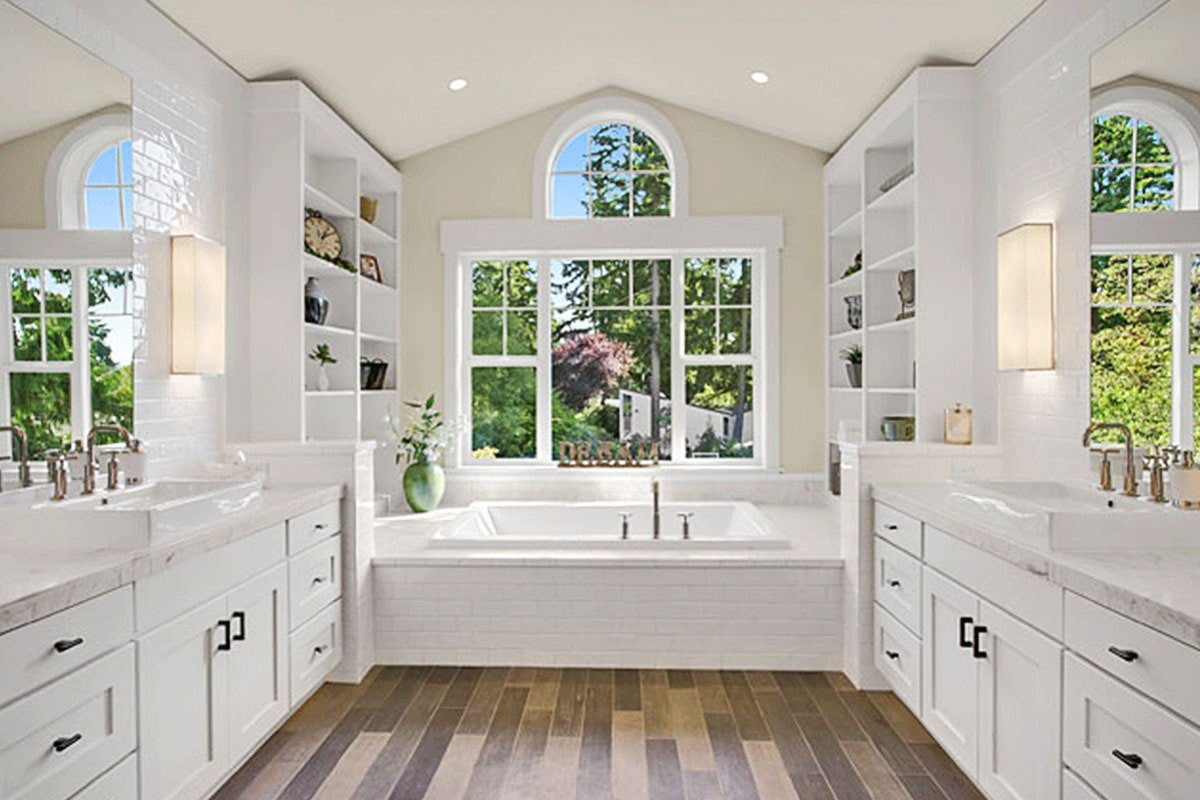 The primary bathroom has his and her vanities, white built-ins, and a deep soaking tub fixed under the Palladian windows.
