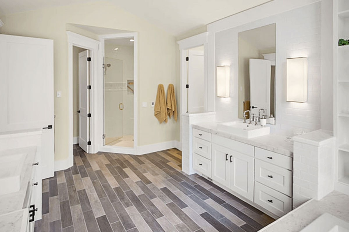 Corner walk-in shower along with a toilet room concealed in the sink vanity complete the primary bathroom.