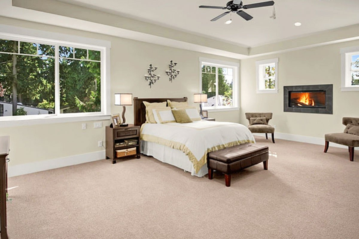 Primary bedroom with a modern fireplace, brown wingback chairs, and a skirted bed with a leather tufted ottoman at its end.