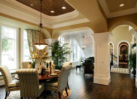 Breakfast nook with striped chairs, a round dining table, and a glass dome pendant that hang from the tray ceiling.