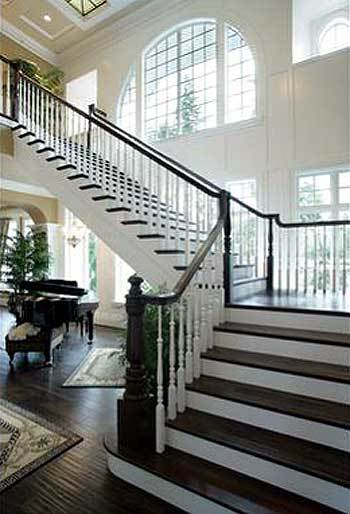 A baby grand piano sits under the half-turn staircase with contrasting white risers and black treads.