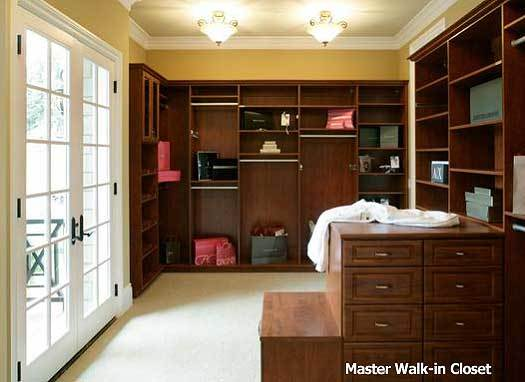 A primary walk-in closet filled with wooden drawers and shelves. French door on the side leads out to the balcony.