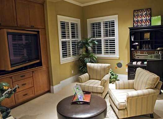 Loft with striped armchairs, round ottoman, dark wood cabinet, TV, and louvered windows.