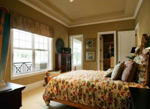 This bedroom has brown walls, a tray ceiling, and a white framed window dressed in a lovely valance.