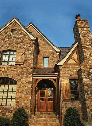 Home entry with a rustic french door framed with decorative wood trims.