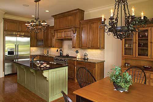 Eat-in kitchen with white subway tile backsplash, wooden cabinetry, and a green beadboard island well-lit by a wrought iron chandelier.