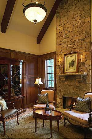 The study has a stone fireplace, round coffee table, cushioned chairs, and a display cabinet that blends in with the wood-paneled walls.