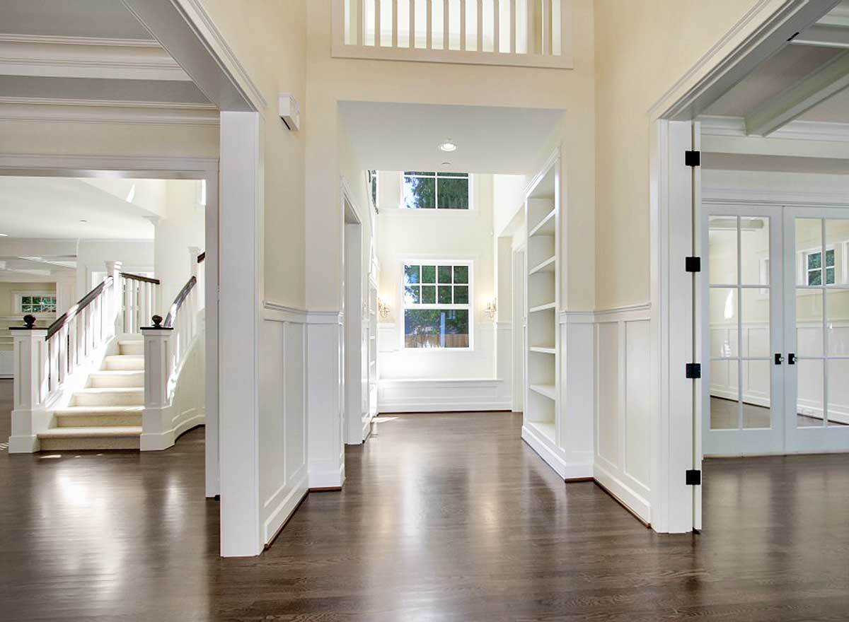 The foyer has dark hardwood flooring and cream walls adorned with white wainscoting.