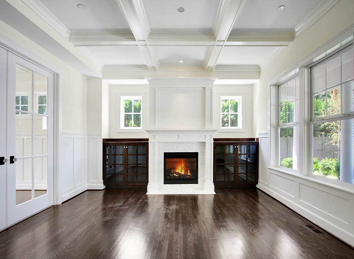 Living room with a french door, coffered ceiling, and a fireplace flanked by glass front cabinets.