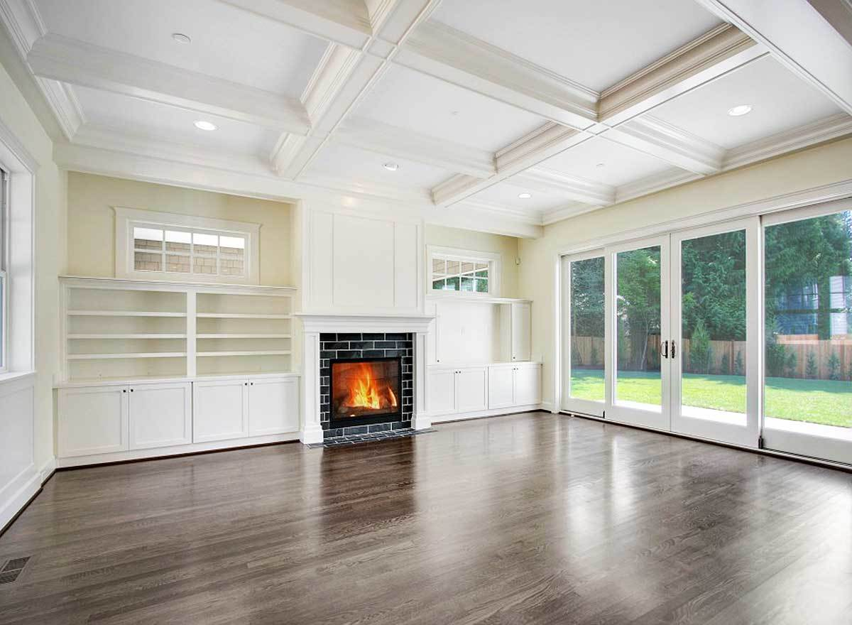 A spacious family room with white built-ins, a fireplace, and a french door that opens out to the patio.