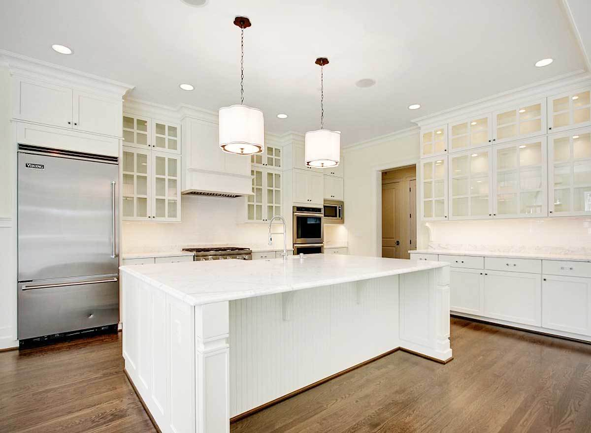 A pair of glass pendants hanging over the marble top island along with recessed ceiling lights illuminate the kitchen.