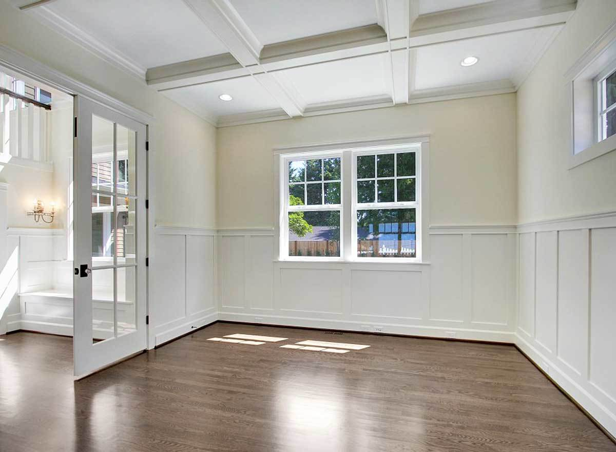 This spare space with coffered ceiling and white wainscoting is dedicated to the home office.