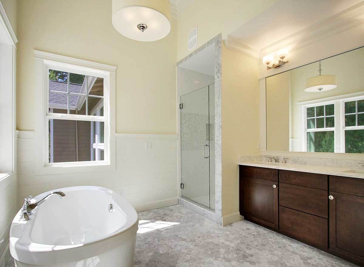 Primary bathroom with a walk-in closet, dual sink vanity, and a freestanding tub illuminated by a drum chandelier.