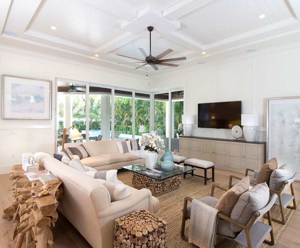 Living room with beige sectionals, cushioned seats, wall-mounted TV, and a fan hanging from the coffered ceiling.