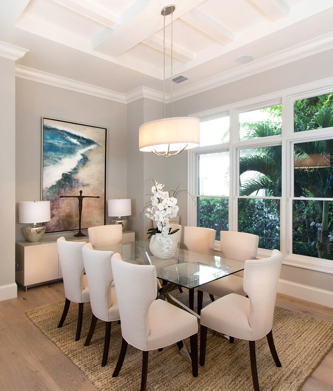 The formal dining room has wingback chairs, a glass top table, a drum chandelier, and a buffet bar adorned with lovely artwork.