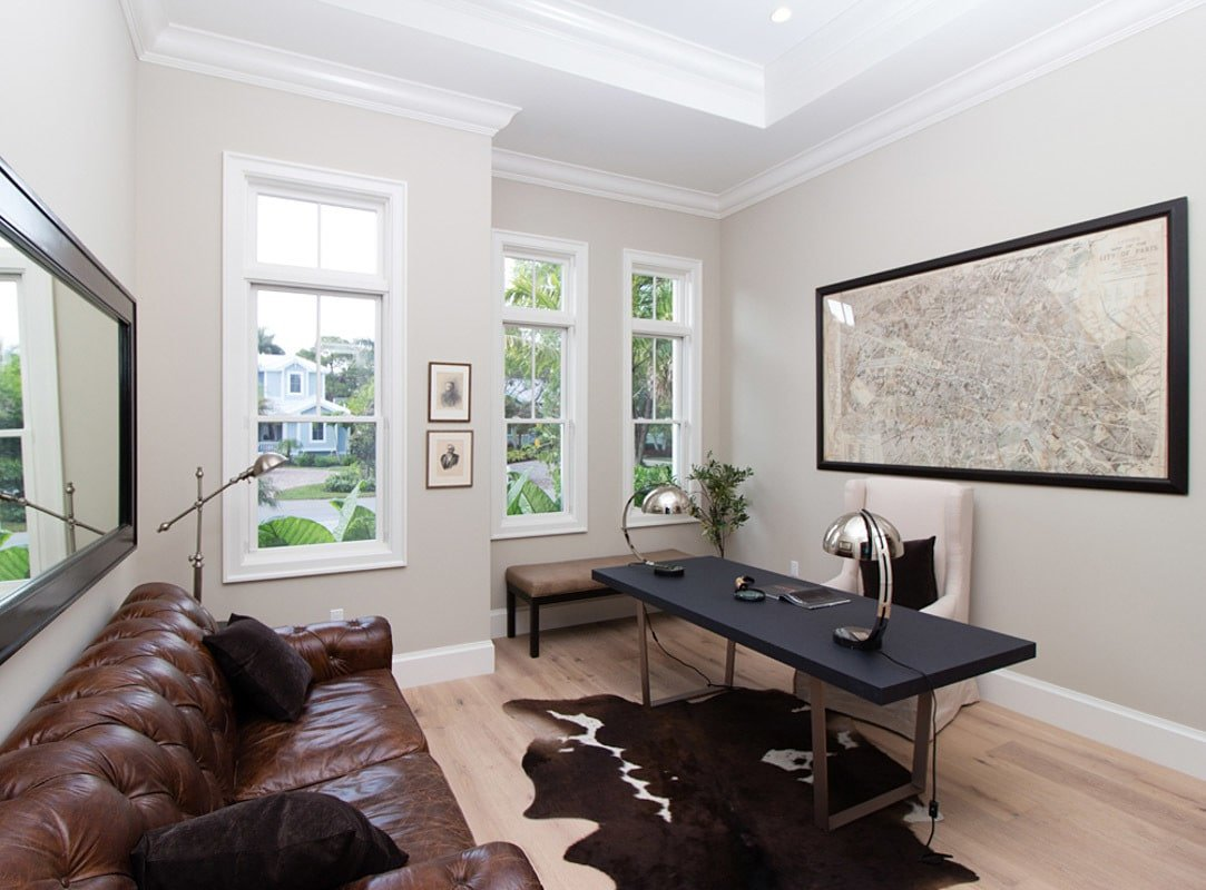 The study has a tray ceiling, a tufted leather sofa, a black desk, a skirted armchair, and a cowhide area rug.