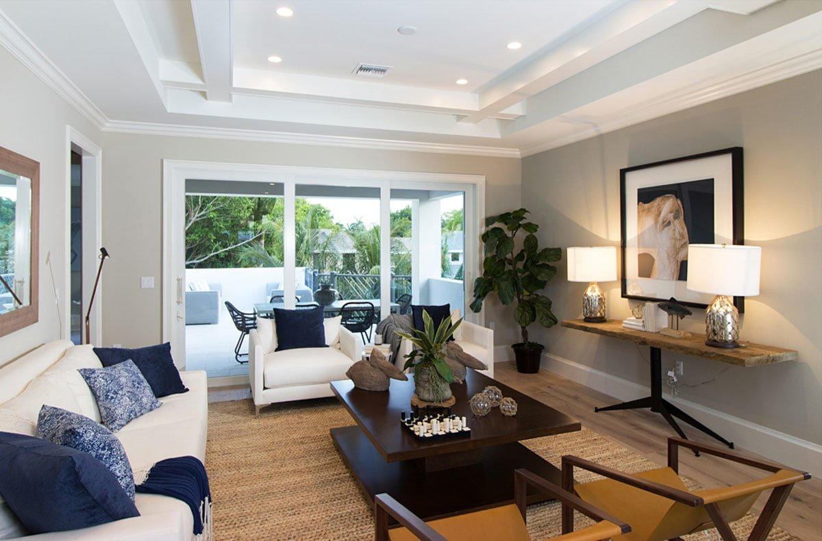 Recreation room with white and brown seats, wooden tables, and a private balcony.