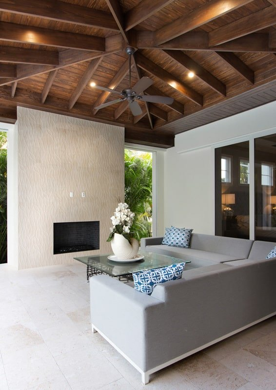 Outdoor living with an L-shaped sofa, a glass top coffee table, and a fireplace.Outdoor living with an L-shaped sofa, a glass top coffee table, and a fireplace.