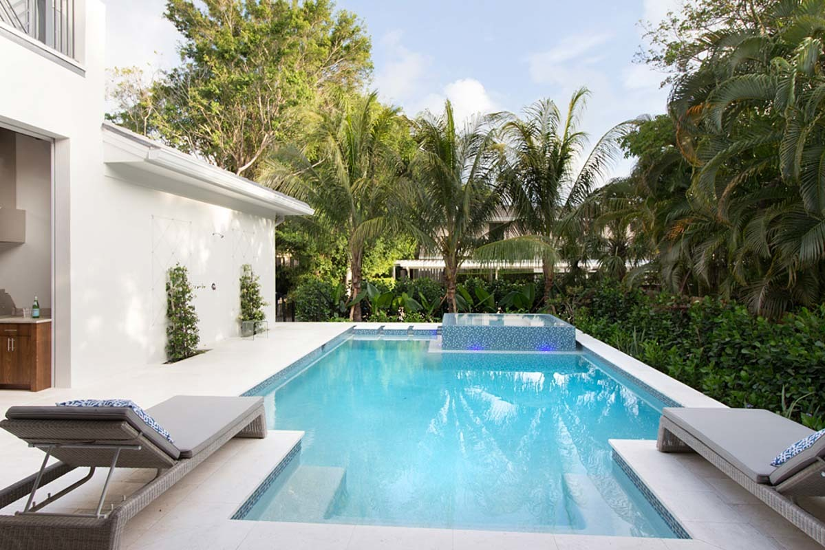 Hedge plants and palm trees surround the backyard pool.