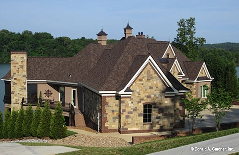 Side exterior view showing the stone brick siding along with gable and hipped roofs topped with cupolas.