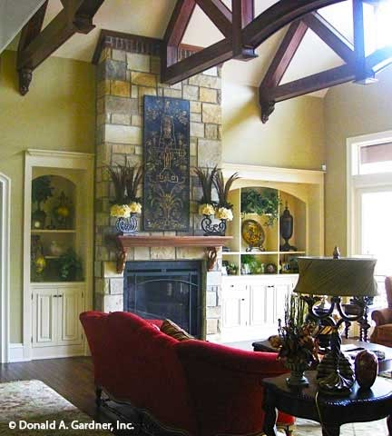The living room has a stone fireplace, white built-ins, and soaring vaulted ceiling framed with exposed wood beams.
