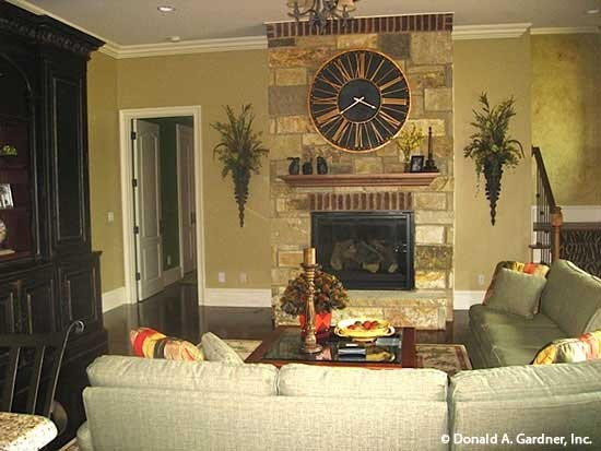 Recreation room with an L-shaped sectional, a glass top coffee table, and a stone fireplace topped by a round wall clock.