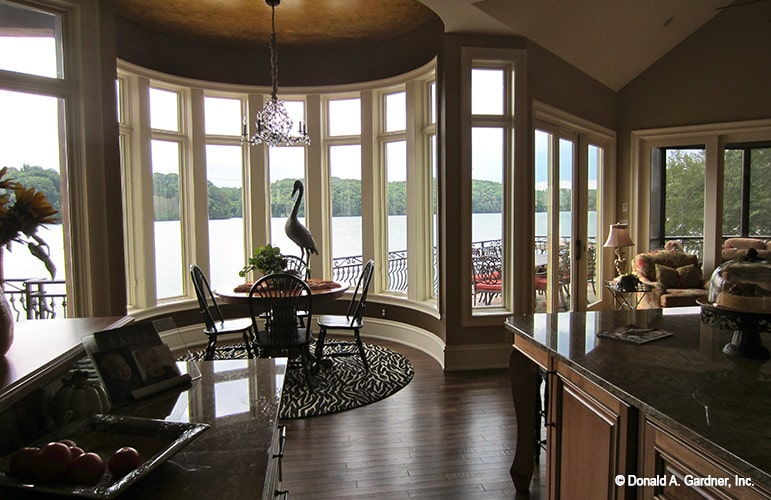 Breakfast nook with round dining set and massive bay window overlooking a magnificent lake view.