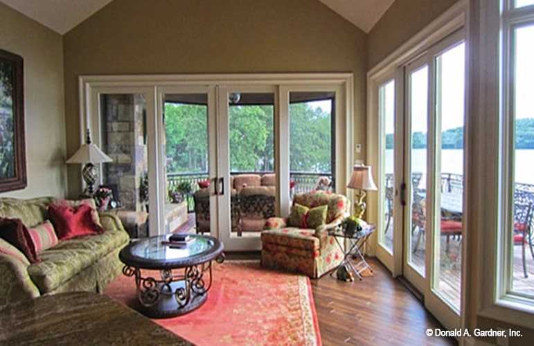 The hearth room has patterned seats, an ornate coffee table, and a french door that opens to the screened porch.