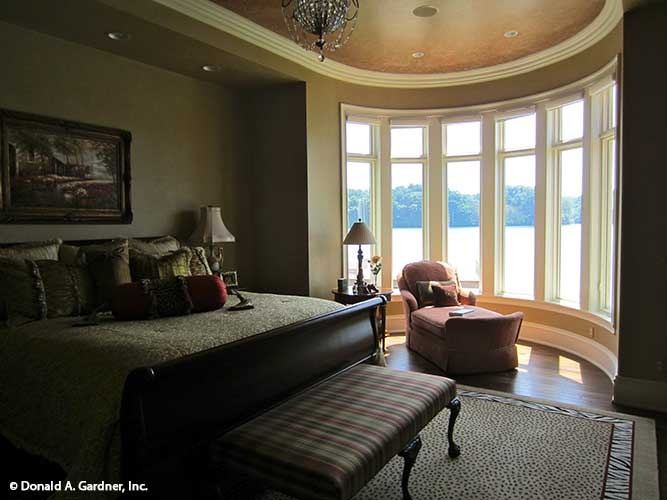 The primary bedroom has dark wood furnishings, chaise lounge by the bay window, and a beaded chandelier hanging from the oval tray ceiling.