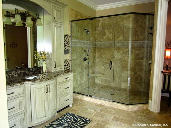 Primary bathroom with a spacious walk-in shower and a granite top vanity complemented with a zebra rug.