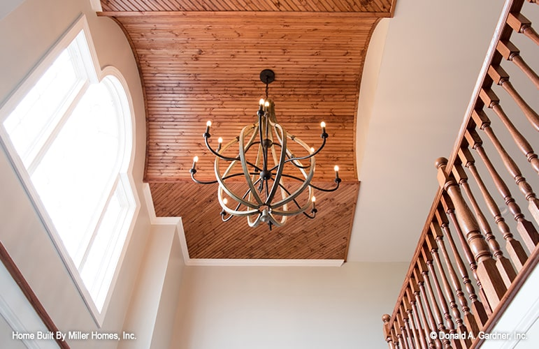Foyer's ceiling clad in wood panels that are mounted with a candle chandelier.