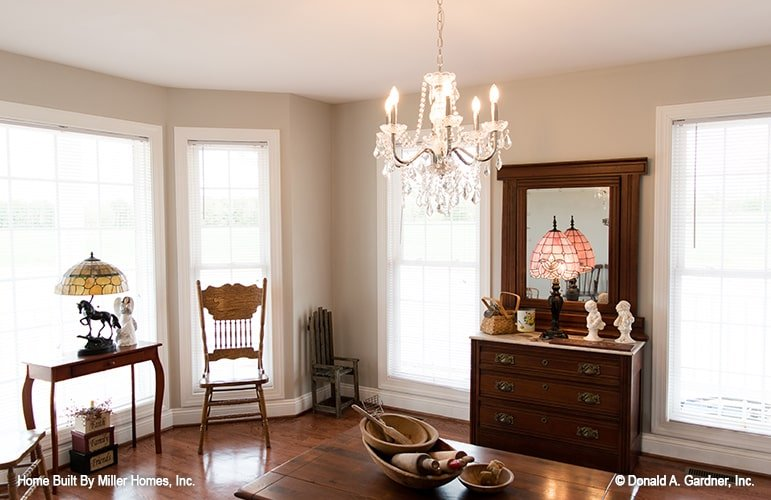 Dining room with bay window, beaded chandelier, and dark wood furnishings that blend in with the hardwood flooring.