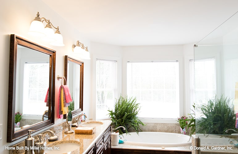 The primary bathroom has his and her vanity, a walk-in shower, and a drop-in bathtub fixed against the bay window.