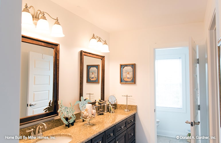 Bathroom with a toilet room and a granite top vanity paired with wooden framed mirrors.