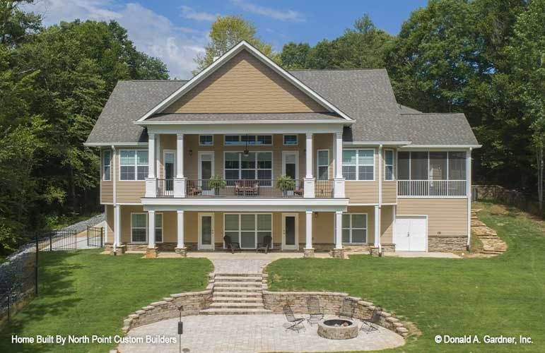 Rear exterior view showing the wide balcony. screened porch, and an open patio with fire pit seating.