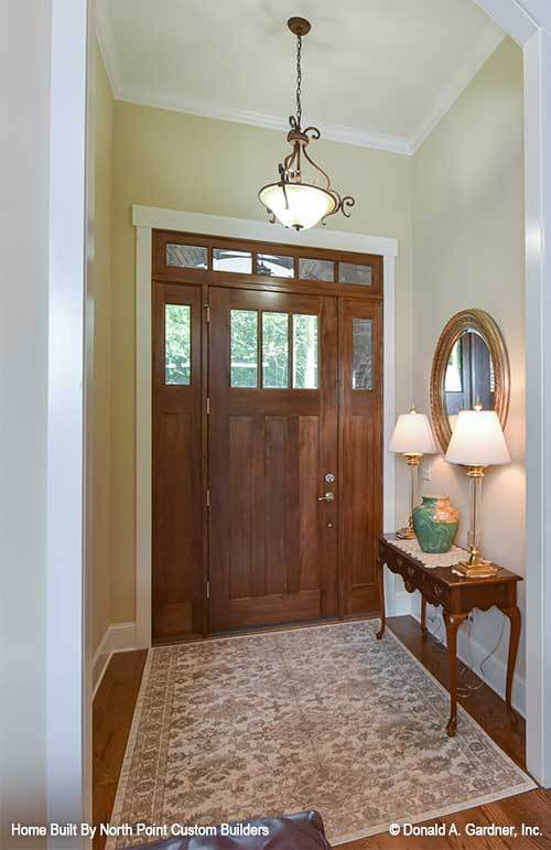 The foyer has a wooden entry door, a floral area rug, and a console table topped by brass lampshades, a ceramic vase, and a round mirror.
