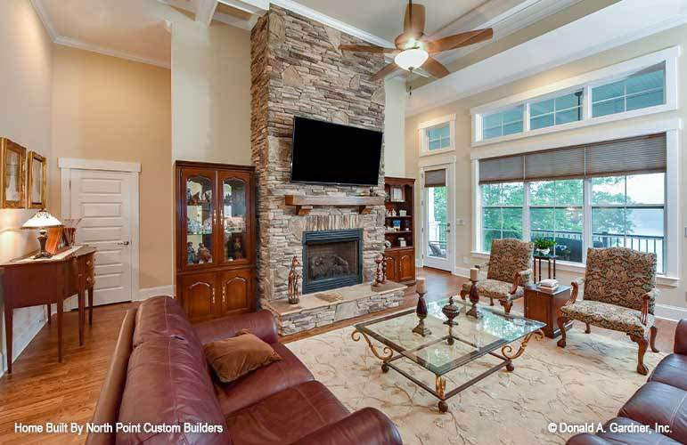 Living room with leather sectionals. patterned armchairs, glass top coffee table, and a stone fireplace with a TV on top.