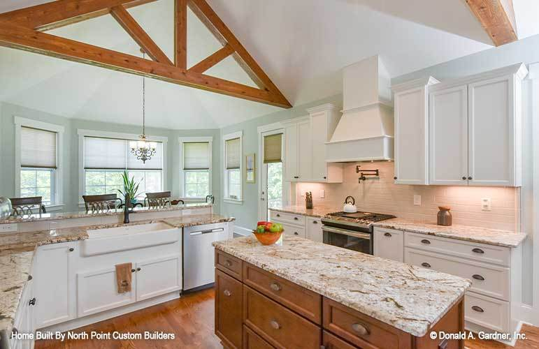 The kitchen has white cabinetry, a farmhouse sink, granite countertops, and a wooden island.