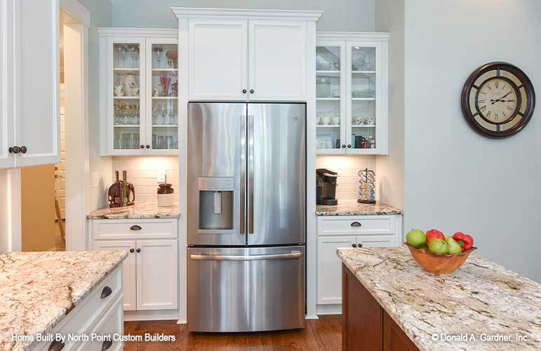 Glass front and white cabinets flank the two-door fridge.