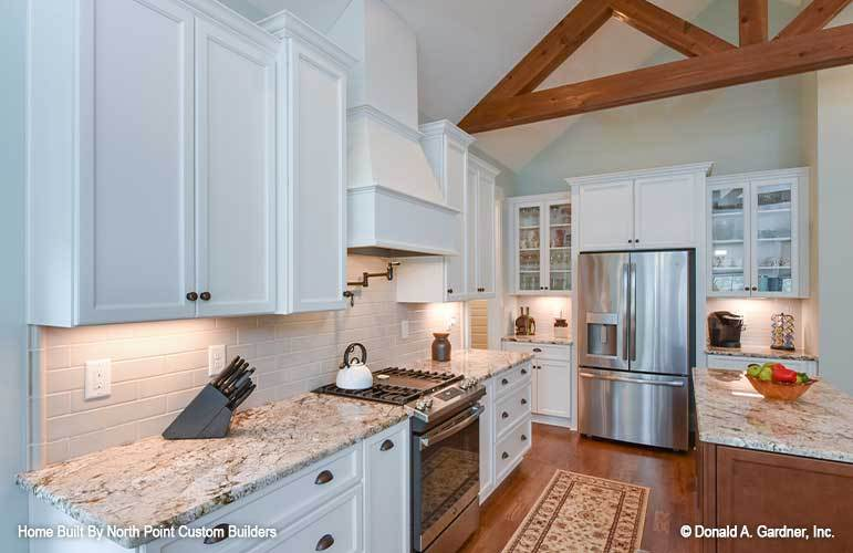A vaulted ceiling with exposed rustic beams crowns the kitchen.