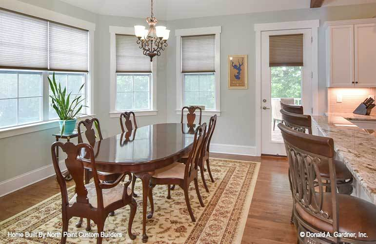 The dining area offers a floral area rug, oval dining set, and an ornate chandelier.