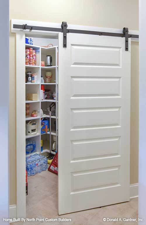 A sliding barn door opens to the walk-in pantry filled with white shelvings.