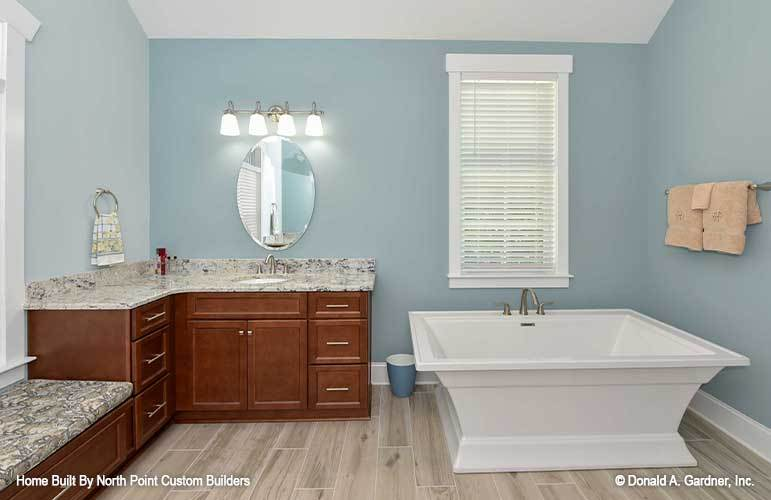 The primary bathroom is equipped with a granite top vanity and a deep soaking tub.