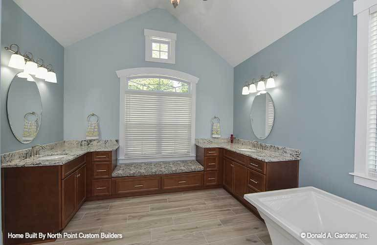 A farther view of the bathroom shows the cathedral ceiling and built-in window seat flanked by his and her vanities.