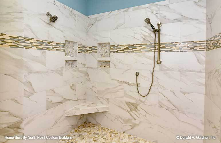Walk-in shower with marble tiled walls, inset shelves, corner seat, and pebble tiled flooring.