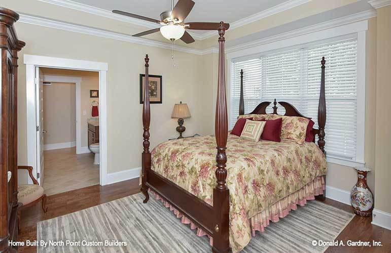 This bedroom has a tray ceiling, a four-poster bed, an antique vase, and a striped rug that lays on the hardwood flooring.