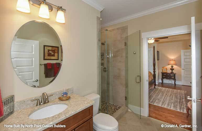 This bathroom offers a walk-in shower, a toilet, and a vanity paired with a round frameless mirror.